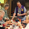 </i>Lion John Cooper assists a group during the Pancake Breakfast.  You may click on any photo to select a larger image.