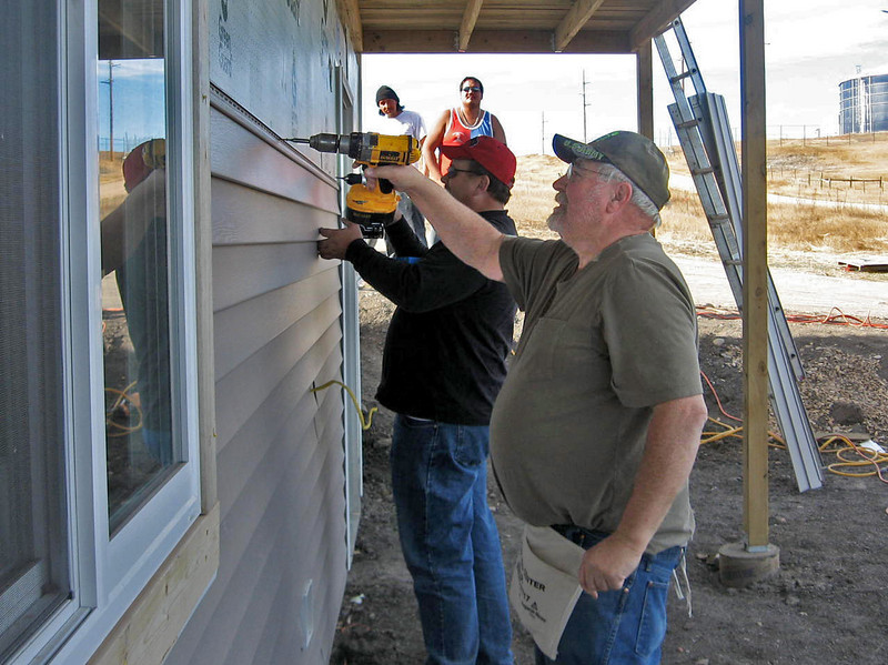 Lions Tom Hood (front) and Duke Boston team up to apply a length of siding.