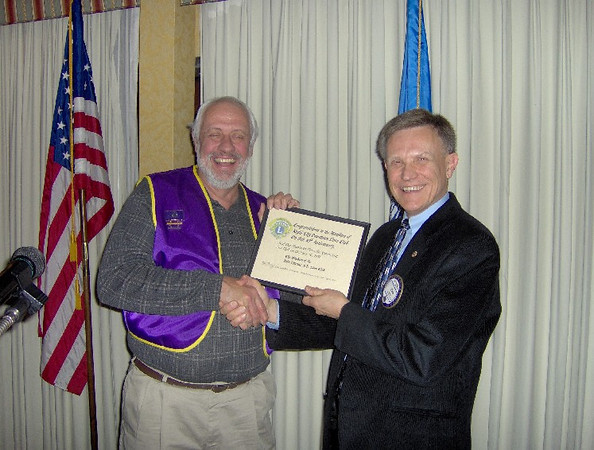 Lion Tom Nary, 2007 president of the Belle Fourche Lions club, presents a 25th anniversary club certificate to an officer of the Piedmont Lions Club, which was originally sponsored by the Belle Fourche Lions.