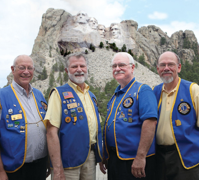 "<b>RUSHMORE LIONS FEATURED IN <i>LIONS</i> MAGAZINE</b>  The Rapid City club was recognized as ""thriving"" and was particularly noted for their <i>Rushmore Lions Nature Park</i>, built in the vicinity of the 1972 flood that took such a high toll in life and property.   A video about the Nature Park can be viewed in the <a href=""http://www.lionsclubs.org/EN/news-and-events/lions-news-network/lq.php?id=c1iDMViH""> Lions Magazine Theater</a>.  The photo in the magazine is shown here.  Pictured (left-to-right) are four past presidents of the Rushmore Lions Club:  Bill Carey, Bob Audette, Dick Waits, and Terry Peterson.  Oh, yes, let us clarify:  they're the smiling presidents in blue vests -- not the stone-faced fellows."
