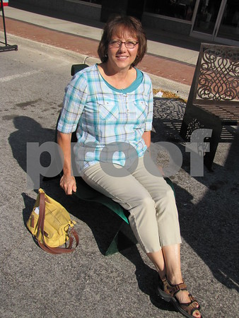 Susan Bush tries out a leaf shaped chair created by Fitzgerald Metals.