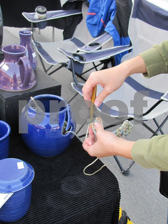 Laura Sandstrom of Miry Clay Pottery demonstrates knitting from a yarn bowl.  The bowl holds the knitter's yarn for her. These bowls and more can be found at Miry Clay Pottery booth during Market on Central.