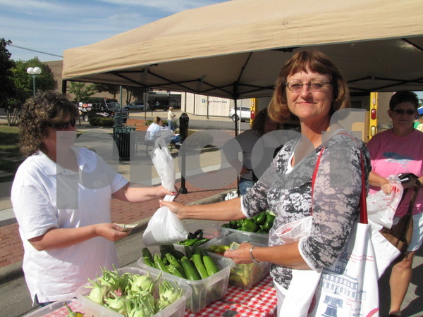 LuAnn Niemand makes a healthy purchase from Dawn Donnelly of Airport Gardens.