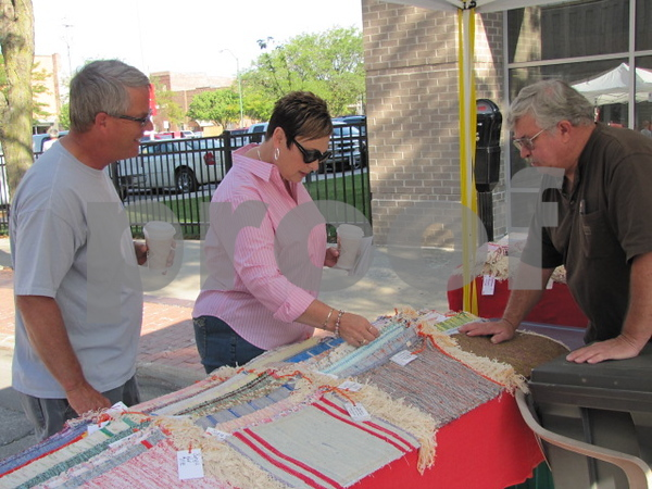 Kevin and Kathy Moe look over some of woven items at Denny Dunbar's booth at Market on Central.