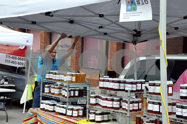 -Messenger photo by Joe Sutter<br /> <br /> Richard Clinefelter, of Gladbrook, helps hold down the Connie's Creation booth during the heavy winds Saturday. His granddaughter works at the booth, owned by Connie Chartier of Norwalk.