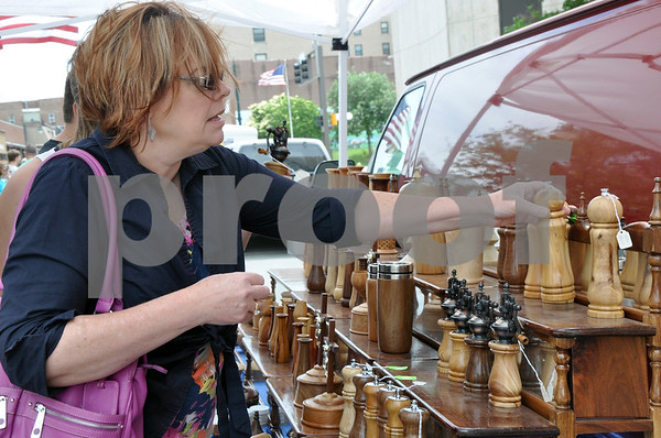 -Messenger photo by Joe Sutter<br /> <br /> Jane Carlon, of Fort Dodge, looks at some wooden salt and pepper grinders for sale at Elegant Wood Turnings, by Paul Peterson of Eagle Grove. Carlon said she liked the market so much last year she wants to come to more of them this year.
