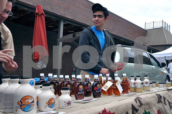 -Messenger photo by Joe Sutter<br /> <br /> Ricardo Ramirez, left, and his son Ricky Ramirez hand out free samples of their maple syrup Saturday at Market on Central. They said it is their first time being at the market, but the will be back again for the rest of the times.