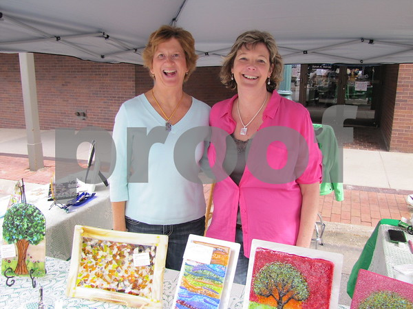 """Tracey Patterson and Kathy Hepburn in Hepburn's booth """"Simply Heaven"""" showcasing fused glass art."""