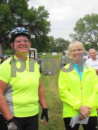 Peg Christensen and Cathy Hugghins listen to the speakers before the start of the pedal power poker ride.