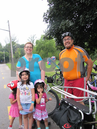 The family of Sarah and George Esper with their children Camille (hiding), Zowi, and Emma before the family bike ride.