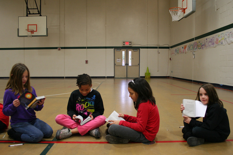 Students look at their dictionaries.