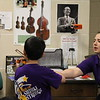 A teacher corrects a Suzuki Strings student.