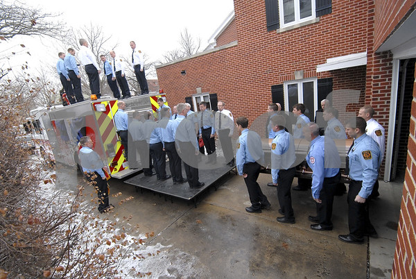-Messenger photo by Hans Madsen<br /> <br /> Fort Dodge firefighters place fellow firefighter Tom Pearts casket on Engine 4 Wednesday morning following a short prayer service at Laufersweiler Seivers Funeral Home.