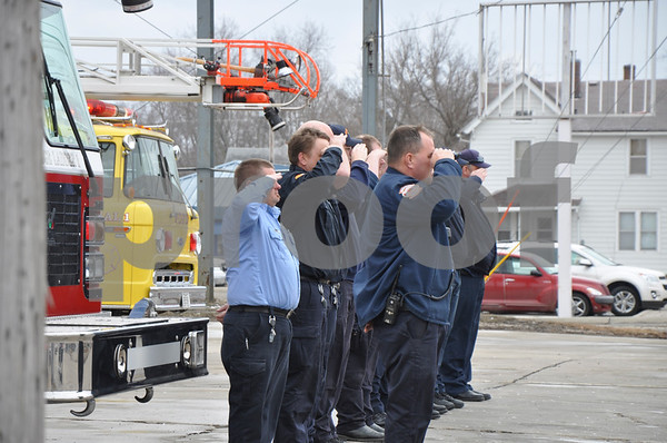 -Messenger photo by Joe Sutter<br /> <br /> Craig Warner, left, and Dustin Pillard of the Mason City Fire Department, along with other out of town firefighters salute the Fort Dodge fire truck bearing Tom Peart's casket.