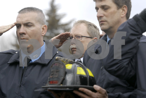 -Messenger photo by Hans Madsen<br /> <br /> Fort Dodge Fire Cpt. Paul Neeson, center, salutes during the graveside services for fellow firefighter Tom Peart Wednesday afternoon at Corpus Christi Cemetery. At left, former Fort Dodge firefighter Jon Bittner salutes while Tom Pille, at right, holds Peart's helmet. Peart died March 14 of an apparent heart attack. He was a 22 year veteran of the department.