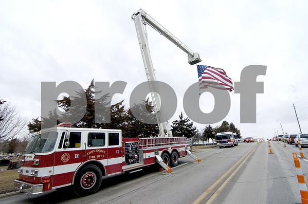 -Messenger photo by Hans Madsen<br /> <br /> The Fort Dodge Fire Department used Snorkel 1 to display a large flag at the entrance to Corpus Christi Cemetery Wednesday afternoon.