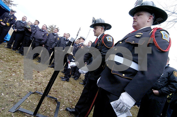-Messenger photo by Hans Madsen<br /> <br /> Sioux City firefighters Justin Oehns, center, rings the bell during the graveside service for Fort Dodge firefigher Tom Peart Wednesday at Corpus Christi Cemetery. The ringing of the bells signify the end of duty and returning to quarters.