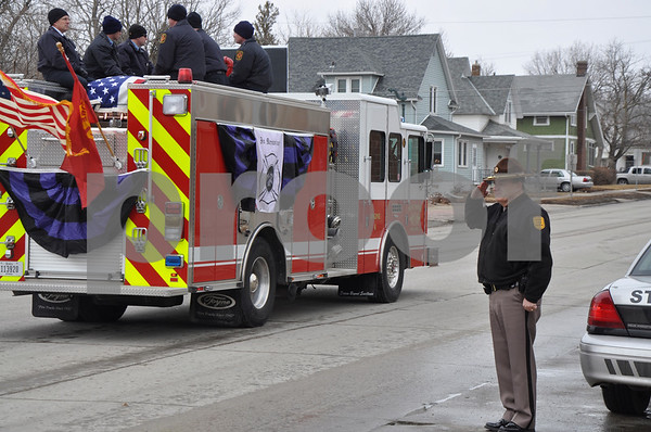 -Messenger photo by Joe Sutter<br /> <br /> Iowa State Trooper Kelly Hindman salutes the fire truck carrying the casket in Tom Peart's funeral procession.