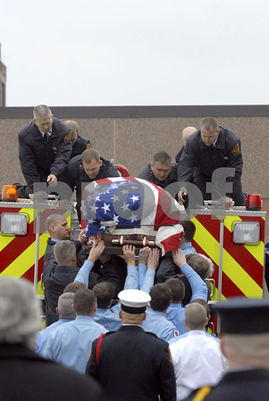 -Messenger photo by Hans Madsen<br /> <br /> Fort Dodge firefighters reach for fellow firefighter Tom Peart's flag draped casket Wednesday afternoon as they prepare to leave Sacred Heart Catholic Church.