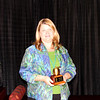 Volunteer holds award for outstanding service.