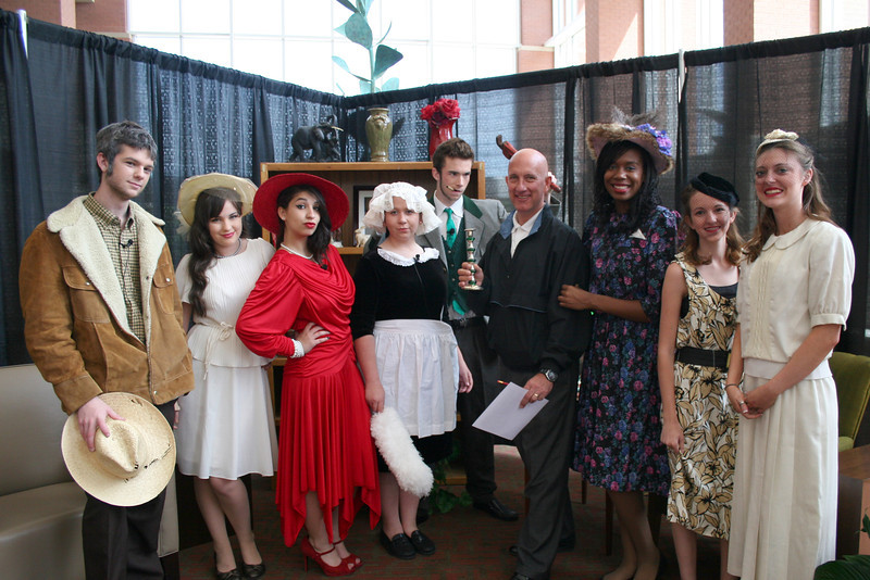 School adopter posing with theatre students dressed as characters from Clue.