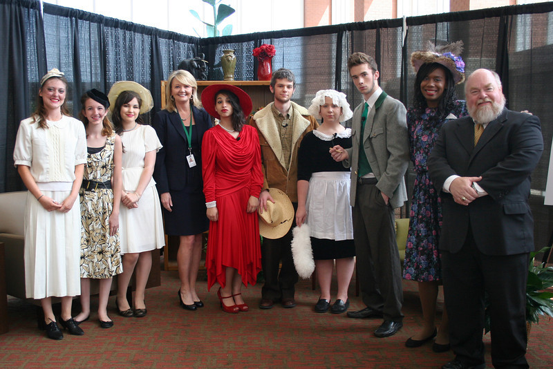 School district officials posing with theatre students dressed as characters from Clue.
