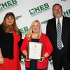 Teri Trammel from Hurst Junior High with school board president Julie Cole and Superintendent Steve Chapman in recognition of the school earning a 2nd place Golden Apple Award.