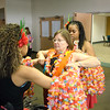 Polynesian dancers put a flower necklace on district official.