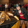 Woman dressed as ringmaster poses with stuffed lion.