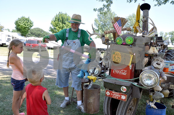 "-Messenger photo by Joe Sutter<br /> <br /> Bob Hill, aka ""Farmer Bob"" of Dysart, inflates a balloon for Kaylee McCane, 9, of Fort Dodge on the left, and Brady Pate, 5, of Badger waits his turn. Hill's old John Deere is covered in antlers, sirens, nicknacks and a little bit of everything - even the kitchen sink. He travels to fairs all across the country."