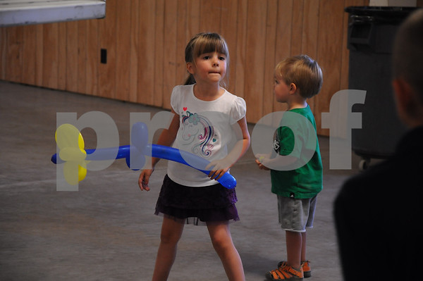 -Messenger photo by Joe Sutter<br /> <br /> Karlee and Kaleb Pearson, 4 and 2, play with a balloon flower while watching Share the Fun at the county fair Sunday.