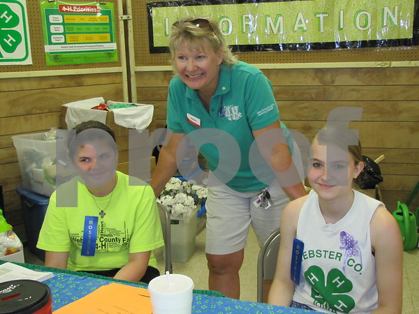 Hostesses Cassidy Wolff and Emma Stuhrenberg with 4-H coordinator Linda Cline in the exhibits building at the Webster County Fair.