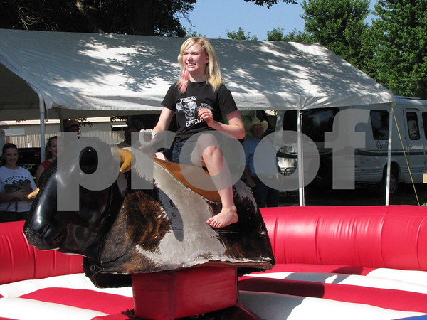 Miranda Keith rides the mechanical bull as her friends and family look on.