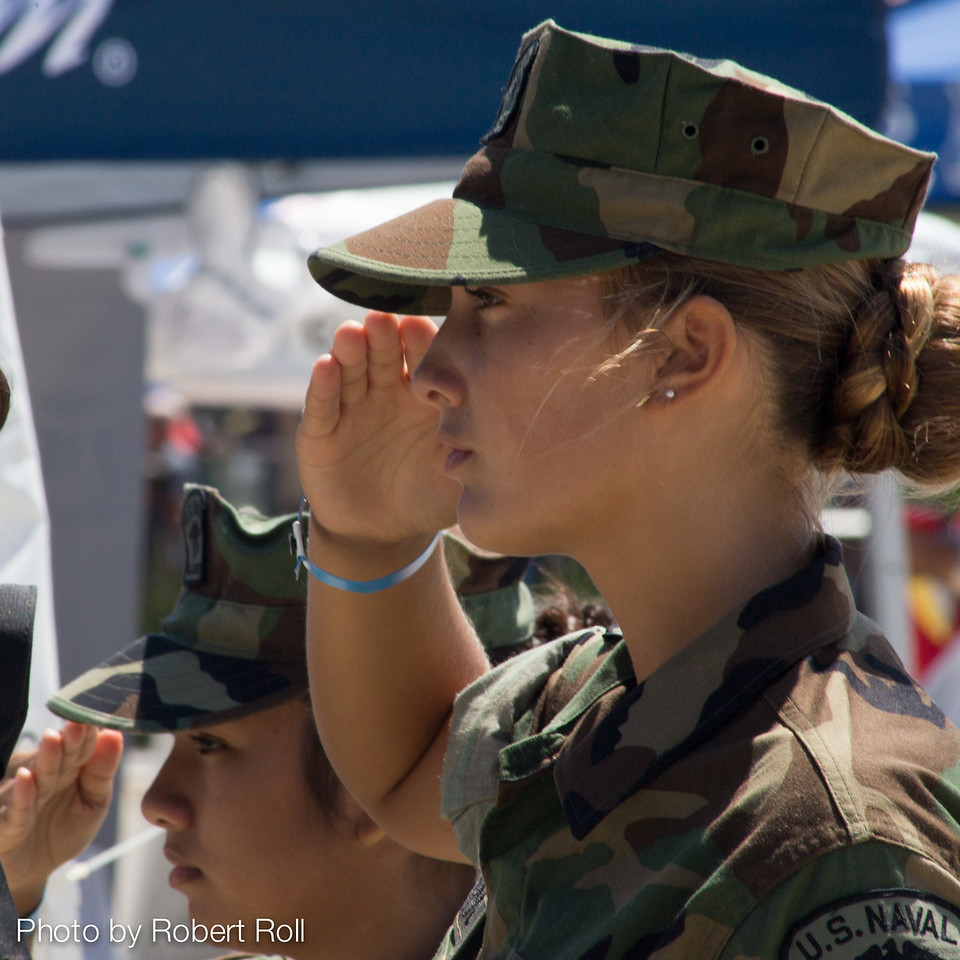 Carmella Loera of Camarillo and Megan Marangola from Newbury Park salute as the National Anthem is played at the 2104 Wings Over Camarillo Air Show.  The women are members of the US Naval Sea Cadets Trident Patrol Squadron 65, which provided support and security for the annual event.