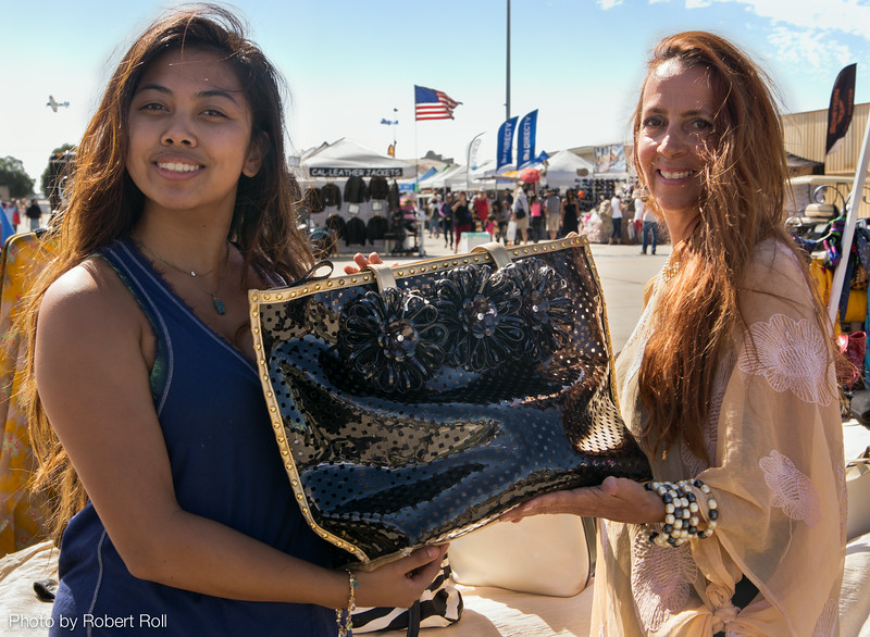 Genica Bungay of Oxnard and Clydia Richardson of Camarillo find a one-of-a-kind handbag to their liking as World War II fighter planes buzz overhead.