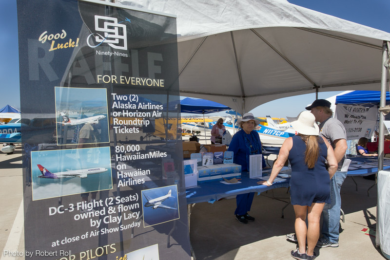 """The Ventura County Ninety-Nines, a nonprofit organization of more than a hundred women pilots, hosted their popular annual raffle on the tarmac of Camarillo Airport.  Member Mariette Coolidge tells visitors that """"the 99s"""" host an annual Girl Scouts in Aviation Day, speaker programs for the local aviation community, paint air markings for local airports and organize a host of other aviation-related activities."""