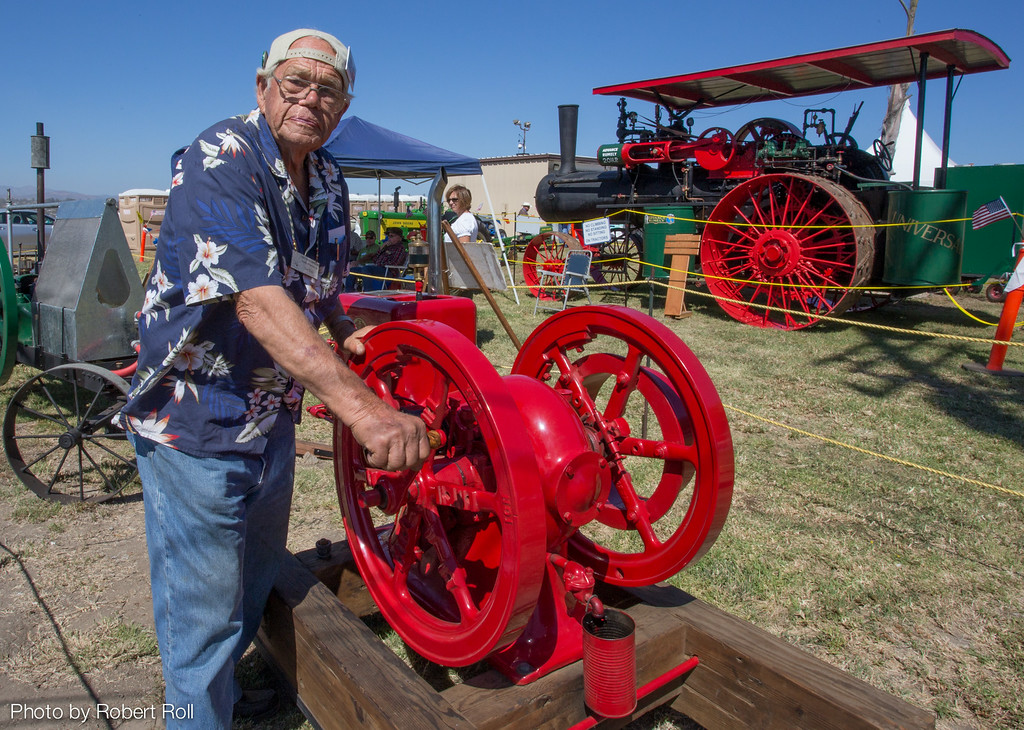 Don Ruby of the Topa Topa Flywheelers coaxes a hundred-year-old International Harvester engine to life while 21st century aircraft zip overhead at the 2014 wings Over Camarillo Air Show.