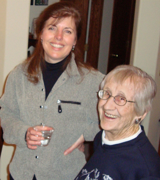 January 11, 2009<br /> <br /> Mary Temple (left) shares a moment with Laura Nelson during a New Year gathering at the Miller's in January 2009.  Laura was an original owner in Yellowstone Place and now hangs her hat at the Hickory House in Spearfish.<br /> <br /> Mary and her husband, Scott, are among the newer residents of the neighborhood. Scott develops computer software; Mary works with Dana Dental in Spearfish.