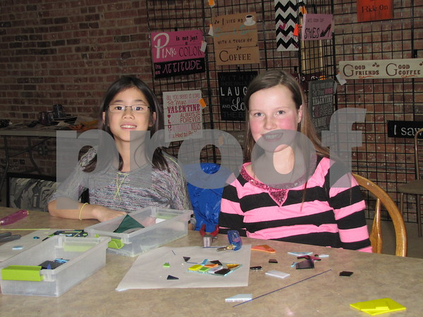 Carley Mullins and Elly Louwagie pose while making their glass creations at Studio Fusion in Fort Dodge.  Louwagie was having her birthday party at Studio Fusion where her guests get to make their own fused glass projects.