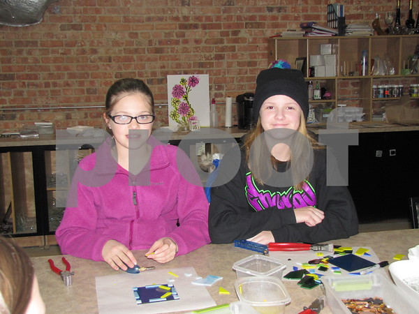 Alexa Chase and Emma Elsbecker make glass creations at a birthday party for their friend held at Studio Fusion in Fort Dodge.