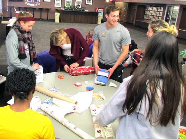 Representatives from UAlbany's Student-Athlete Advisory Committee support Albany County's 'Adopt-a-Family' initiative by wrapping gifts for local families in need.