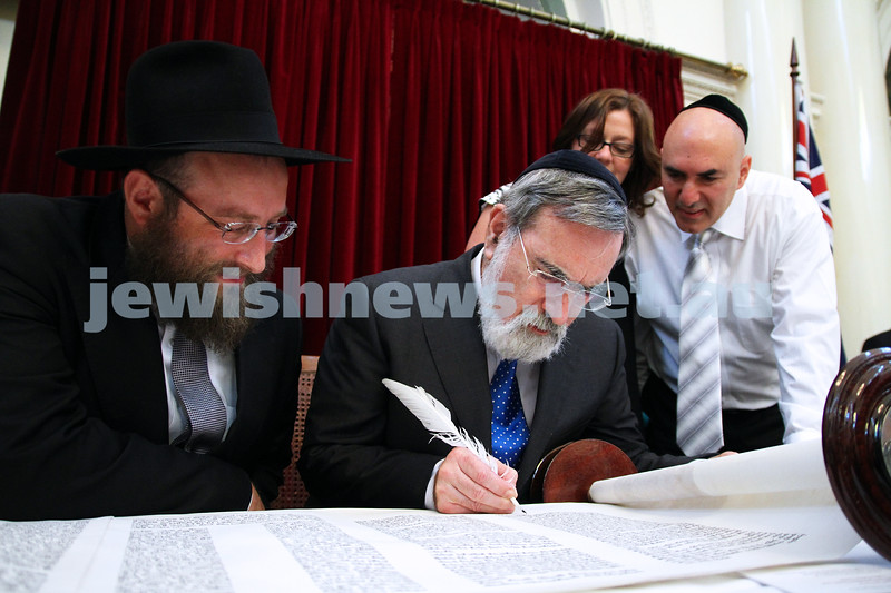 29-1-12. East Melbourne Hebrew Congregation. Double Torah dedication at Queens Hall, Parliament House, Victoria with Chief Rabbi Lord Jonathan Sacks in attendance. Lord sacks filling in the last letter of the new torah. Rabbi Eli Gutnick (left) and EMHC president Danny Segal looking on. Photo: Peter Haskin.