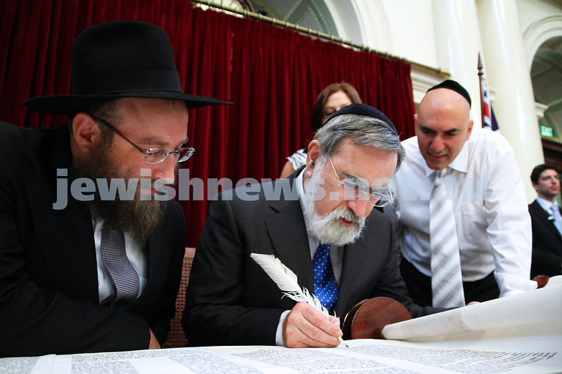29-1-12. East Melbourne Hebrew Congregation. Double Torah dedication at Queens Hall, Parliament House, Victoria with Chief Rabbi Lord Jonathan Sacks in attendance. Lord Sacks filling in last letter of the new torah. Rabbi Eli Gutnick (left) and EMHC president Danny Segal looking on. Photo: Peter Haskin.