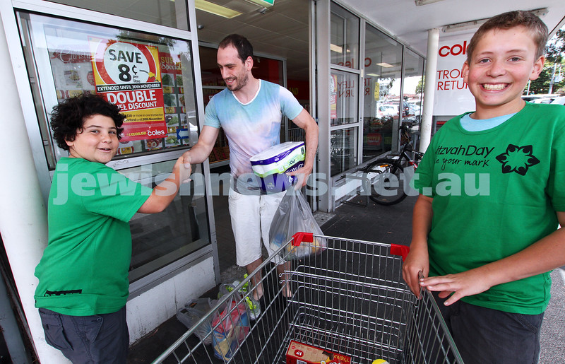 25-11-12. Mitzvah Day 2012. Isaac Zahavi (left) and Noah DeBortoli thank a Coles shopper for the food donation.  Photo: Peter Haskin