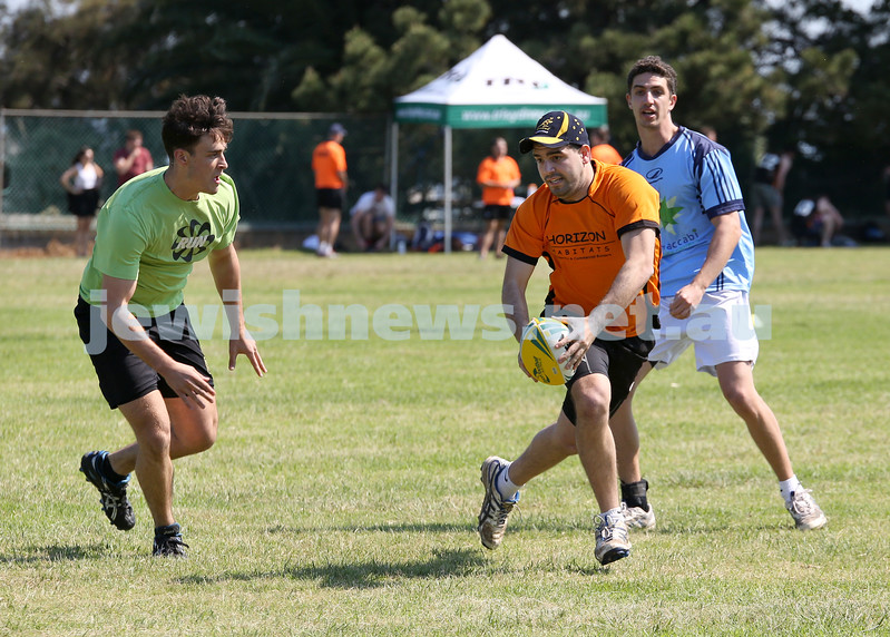 Maccabi Touch Footy competition at Centennial Park. Horizon Habitats (orange) vs Prestige Worldwide (green). Simon Molner runs with the ball as he is blocked by Jack Symonds.