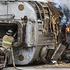 A Logansport firefighter sprays down the train car at One General St. on Wednesday, June 23, 2021 in Logansport.