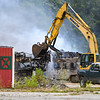 An excavator pulls a train car that is on fire onto its side at One General St. on Wednesday, June 23, 2021 in Logansport.