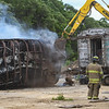 An excavator tears off metal from the train car on Wednesday, June 23, 2021 in Logansport.
