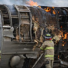 A Logansport firefighter pulls off insulation from the burning train car at One General St. on Wednesday, June 23, 2021 in Logansport.