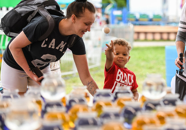 Qhalid Morrison, 3, throws a ping pong ball in hopes of winning a fish with the help of his mom Karina during the opening day of the Cass County Fair in Logansport on Sunday, July 11, 2021.